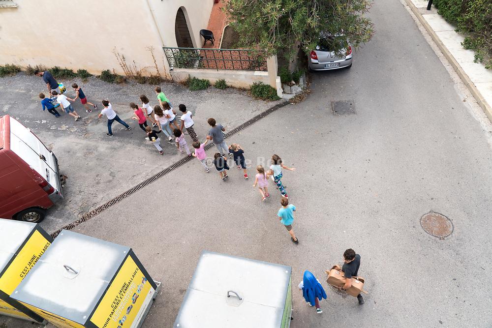 school children group walking in the street with teachers, rural France