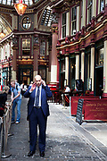 Businessman on his cell phone in Leadenhall Market in the City of London. Located in Gracechurch Street, the market dates back to the fourteenth century. There are cheesemongers, butchers and florists. Originally a meat, game and poultry market, it stands on what was the centre of Roman London. Designed in 1881 by Sir Horace Jones.