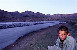A young boy sits near the Kokcha River