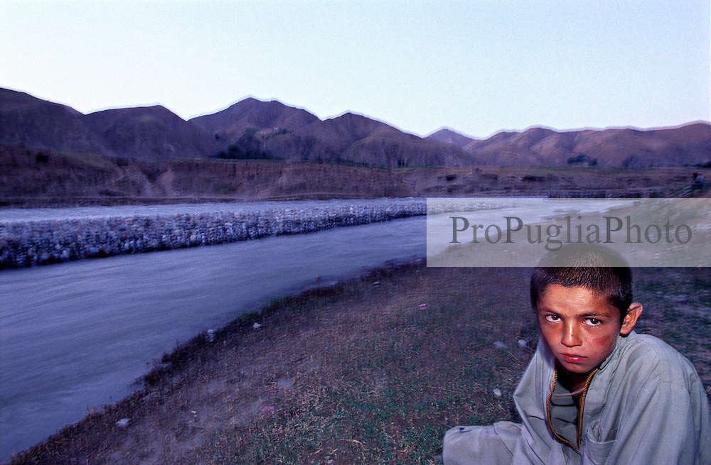 A young boy sits near the Kokcha River