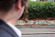 'Jihad 4 Israel'.  An Orthodox Jewish man walking past anti semitic graffiti on a wall in Leweston Place, Stamford Hill, London.