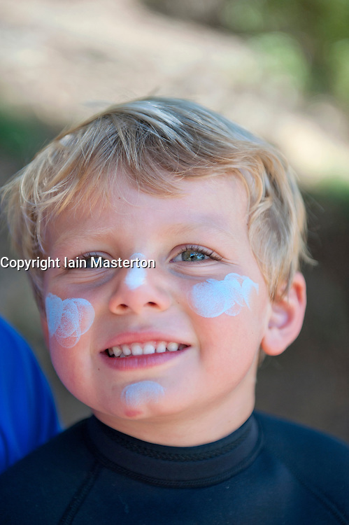 Portrait of young Australian boy with blue sunblock cream on his face