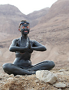 Israel, Dead Sea, tourist cover herself in therapeutic mud in order to benefit from claimed skin care properties of this mud.