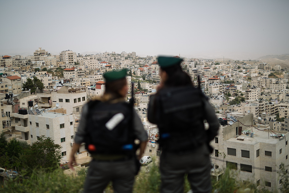 Israeli Border Police Women Staff Sergeant Chen Cohen (L) and Corporal Mor Hadad (R) are seen as they take post on a hill overlooking the East Jerusalem neighborhood of Issawiya, near the Mt Scopus campus of the Hebrew University, in Jerusalem, Israel, on April 10, 2016.