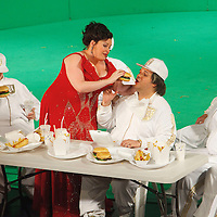 Picture shows : Tiziano Bracci as Mustafa being fed burgers by Karen Cargill as Isabella. Thomas Walker as Lindoro standing left..Picture  ©  Drew Farrell Tel : 07721 -735041..A new Scottish Opera production of  Rossini's 'The Italian Girl in Algiers' opens at The Theatre Royal Glasgow on Wednesday 21st October 2009..(Soap) opera as you've never seen it before..Tonight on Algiers.....Colin McColl's cheeky take on Rossini's comic opera is a riot of bunny girls, beach balls, and small screen heroes with big screen egos. Set in a TV studio during the filming of popular Latino soap, Algiers, the show pits Rossini's typically playful and lyrical music against the shoreline shenanigans of cast and crew. You'd think the scandal would be confined to the outrageous storylines, but there's as much action off set as there is on.....Italian bass Tiziano Bracci makes his UK debut in the role of Mustafa. Scottish mezzo-soprano Karen Cargill, who the Guardian called a 'bright star' for her performance as Rosina in Scottish Opera's 2007 production of The Barber of Seville, sings Isabella..Cast .Mustafa...Tiziano Bracci.Isabella..Karen Cargill.Lindoro...Thomas Walker.Elvira...Mary O'Sullivan.Zulma...Julia Riley.Haly...Paul Carey Jones.Taddeo...Adrian Powter..Conductors.Wyn Davies.Derek Clarke (Nov 14)..Director by Colin McColl.Set and Lighting Designer by Tony Rabbit.Costume Designer by Nic Smillie..New co-production with New Zealand Opera.Production supported by.The Scottish Opera Syndicate.Sung in Italian with English supertitles..Performances.Theatre Royal, Glasgow - October 21, 25,29,31..Eden Court, Inverness - November 7. .His Majesty's Theatre, Aberdeen  - November 14..Festival Theatre,Edinburgh - November 21, 25, 27 ...Note to Editors:  This image is free to be used editorially in the promotion of Scottish Opera. Without prejudice ALL other licences without prior consent will be deemed a breach of copyright under the 1988. Copyright Design and Patents Act  and will be sub
