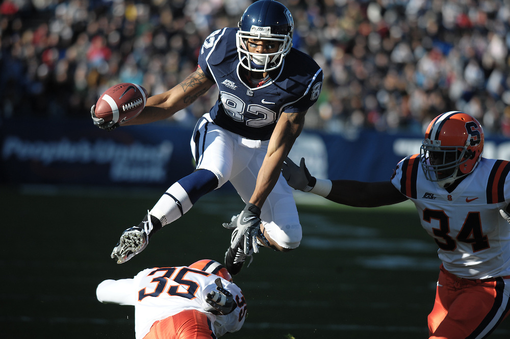 Connecticut's Kashif Moore top, leaps over Syracuse's Mike Holmes, bottom, while pursued by E.J. Carter, right, during the first half of an NCAA college football game at Rentschler Field in East Hartford, Conn. Moore reached the two yard line on the play.  (AP Photo/Jessica Hill)