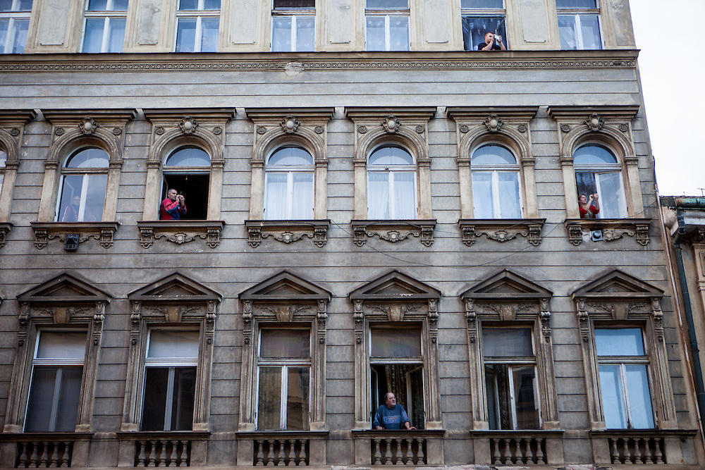 Prague citizens watching an anti-Islam rally in the streets underneath their building. Czech Republic celebrates that day the 26th anniversary of the Velvet Revolution which took place in 1989.