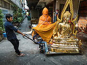 09 MARCH 2016 - BANGKOK, THAILAND:  A worker pulls a statue of the Buddha down an alley next to Thanon Bamrung Muang in Bangkok. The street is lined with workshops that make statues of the Buddha and revered Thai Buddhist monks. Once located just outside Bangkok's city walls, it's now in the heart of the city.    PHOTO BY JACK KURTZ