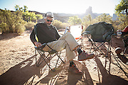 SHOT 10/15/16 9:08:01 AM - Paul Hobson of Steamboat Springs, Co. licking his wounds after a long night around the campfire during a White Rim mountain biking trip in Canyonlands National Park just outside of Moab, Utah. The White Rim Road is a 71.2-mile-long unpaved four-wheel drive road that traverses the top of the White Rim Sandstone formation below the Island in the Sky mesa of Canyonlands National Park in southern Utah in the United States. The road was constructed in the 1950s by the Atomic Energy Commission to provide access for individual prospectors intent on mining uranium deposits for use in nuclear weapons production during the Cold War. Four-wheel drive vehicles and mountain bikes are the most common modes of transport though horseback riding and hiking are also permitted.<br /> (Photo by Marc Piscotty / © 2016)