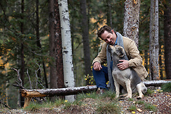 man enjoying time alone with his  dog outdoors in the woods of New Mexico