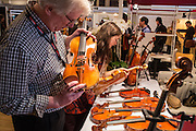 Visitors examine violins. Violins at Mondomusica ranged from basic student instruments to rare vintage violins.