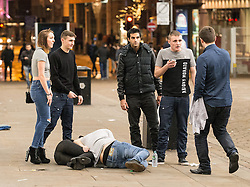 © Licensed to London News Pictures . 01/01/2015 . Manchester , UK . A man lies on the ground and tends to a woman who is collapsed on the ground . Revellers usher in the New Year on a night out in Manchester City Centre .  Photo credit : Joel Goodman/LNP