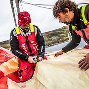 Leg 7 from Auckland to Itajai, day 12 on board MAPFRE, Xabi Fernadez cutting a piece of 3Di from the sail A3 with the help of Guillermo Altadill to repair the main sail, 29 March, 2018.