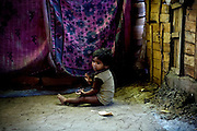 A malnourished child is sitting in a corner of his makeshift home while eating a piece of stale chapatti (Indian bread) in Oriya Basti, one of the water-affected colonies near the abandoned Union Carbide (now DOW Chemical) industrial complex in Bhopal, Madhya Pradesh, India, site of the infamous 1984 gas tragedy. The poisonous cloud that enveloped Bhopal left everlasting consequences that today continue to consume people's lives.