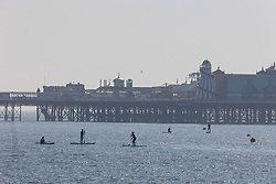 Licensed to London News Pictures. 07/09/2021. Brighton, UK. Paddle boarders cool off in the sea at Brighton Beach, East Sussex as weather forecaster predict a scorching 30c high today with September temperatures expecting to hit over 29c tomorrow. Photo credit: Alex Lentati/LNP