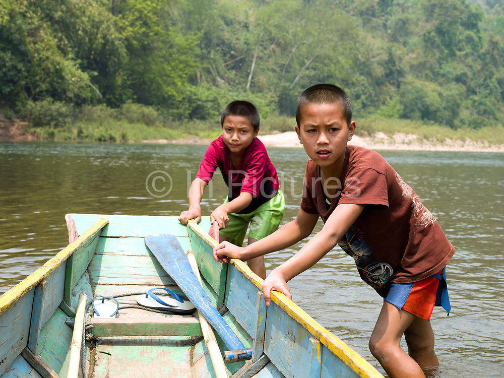 """Two boys, Sone (13) and Sengpheth (10) push a boat to the edge of the Nam Ou river, Phongsaly province, Lao PDR. The Nam Ou river connects small riverside villages, but this river and others like it, that are the lifeline of rural communities and local economies are being blocked, diverted and decimated by dams. The Lao government hopes to transform the country into """"the battery of Southeast Asia"""" by exporting the power to Thailand and Vietnam."""