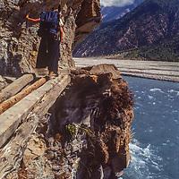 A trekker navigates a log bridge beside the Kali Gandaki River in Nepal.