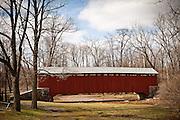 Amish women rides her bike through Pool Forge Covered Bridge Caenarvon Township, PA