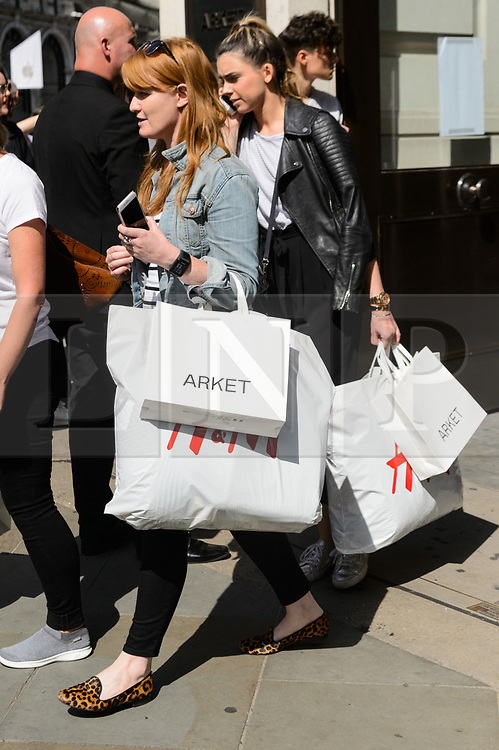 © Licensed to London News Pictures. 25/08/2017. London, UK. Customers leaving with shopping bags at the opening of H&M group's first ARKET flagship clothing store in Regent Street. ARKET has called itself a modern day market seeing not only clothes, but homeware as well as a small cafe space. Photo credit: Ray Tang/LNP