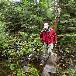 A hiker crosses the start of the Connecticut River just below Fourth Connecticut Lake in Pittsburg, New Hampshire.