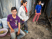 04 SEPTEMBER 2013 - BANGKOK, THAILAND:  Cambodian workers relax after the construction shift at the construction site of a new high rise apartment / condominium building on Soi 22 Sukhumvit Rd in Bangkok. The workers live in the corrugated metal dorms on the site. Most of the workers at the site are Cambodian immigrants.    PHOTO BY JACK KURTZ