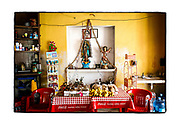 SHOT 2/21/19 1:54:48 PM - A small indoor capilla set up inside a roadside convenience store in San Antonio Cámara in the Yucatan Peninsula of Mexico. An Our Lady of Guadalupe statue oversees a display of shoes and bananas inside the store. Our Lady of Guadalupe is a powerful and ubiquitous symbol of Mexican identity because some guess that Our Lady of Guadalupe's skin tone matches that of Mexico's indigenous population: light brown. She is as much revered for her striking similarity to the vanquished native Mexican population as she is for being the mother of God. (Photo by Marc Piscotty / © 2019)