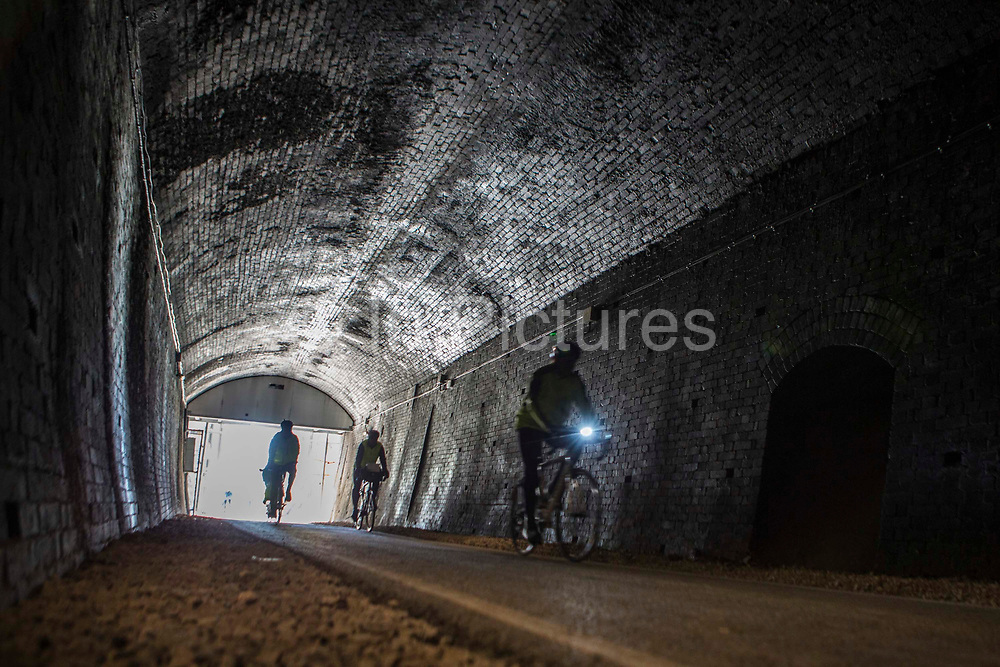 Cyclists ride through the restored Devonshire Tunnel which is part of the Two Tunnels Greenway near Bath, Somerset, England, United Kingdom on 6th April 2013.  The tunnel is 407 meters long and has been restored so it is accessible by foot, cycle or wheelchair and well light throughout.  The tunnel was previously part of a main railway line, the walls are blackened with a thick crust of soot from engine exhaust, while a strip in the roof is blasted clean by that same exhaust.  The tunnel is stone-lined throughout and on a curved and falling 1:50 gradient.  The tunnel is part of a 13-mile route and was restored by Sustrans in partnership with Bath and North East Somerset Council.  The opening of the route was attended by hundreds of cyclists and pedestrians to celebrate the new access to beautiful Somerset country-side.