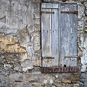 Old window blends in with the rest of the mid-tones on this wall. Roissy-en-France, France.