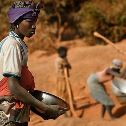 Goubre, Burkina Fasso, Décembre 2007, situé dans le Nord Sahel du Burkina Faso, sur le territoire du village de Goubre. Fréquenté par les fermiers des alentours et accessible à tous sans droits d'exploitations..D'abord, les hommes creusent des trous d'environ dix mètre de haut. Ensuite, les enfants chargé de creuser les galleries horizontales commencent leur travail..Le sterrers sont ramenées à la surface dans des sacs et des bidons. Les femmes fouillent la terre au moyen de bassines pour trouver les pépites d'or..A la tombée du jour, les acheteurs d'or font le tour des mineurs pour acheter le travail de la journée. L'or est pesé au moyen de petite ballance..Les conditions de travail sont difficiles et dangereuses..Les galleries ne sont pas étanconnées. Les éboullements sont fréquents. © SCORPIX / Fred Guerdin.