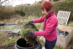 Woman filling compost bin on allotment.