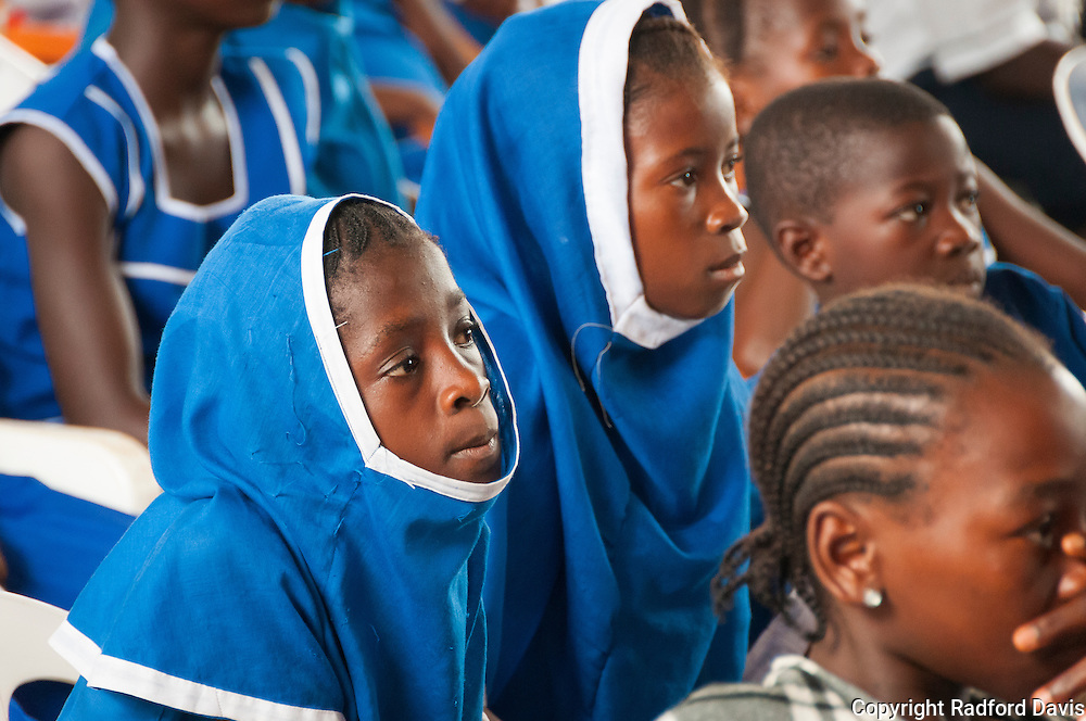 School girls in Sierra Leone learning about dog bites and rabies during World Rabies Day. Here, young muslim girls watch the skits on stage.
