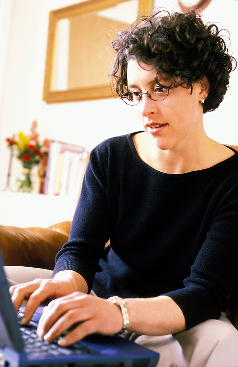 A woman in her home intently typing on a laptop computer.