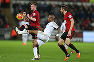 Chris Brunt of West Bromwich Albion (l) is challenged by Andre Ayew of Swansea city (c). Barclays Premier league match, Swansea city v West Bromwich Albion at the Liberty Stadium in Swansea, South Wales  on Boxing Day Saturday 26th December 2015.<br /> pic by  Andrew Orchard, Andrew Orchard sports photography.