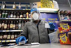 © Licensed to London News Pictures. 19/04/2020. Fetcham, UK. The owner of the Holiday News newsagents shop wears full protective face mask, visor and gloves as he serves customers in Fetcham, Surrey. The government have announced that lockdown will continue for another three weeks. The public have been told they can only leave their homes when absolutely essential, in an attempt to fight the spread of the coronavirus COVID-19 disease. Photo credit: Peter Macdiarmid/LNP