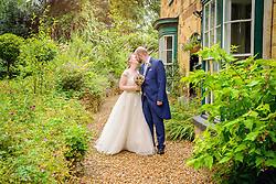 Bride and Groom kissing in the gardens at the Barns, Hunsbury Hill