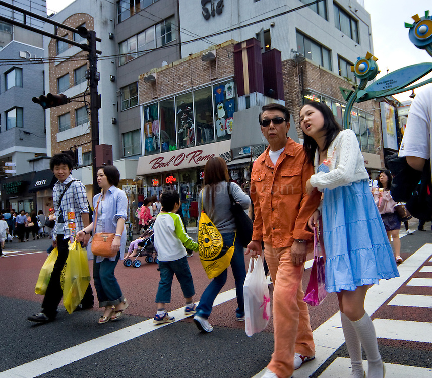 """Older man and younger woman crossing a street in Harajuku, Tokyo, Japan. Harajuku is reknowned for its outrageous youth fashions and """"bo beep"""" girls. Editorial Only.."""