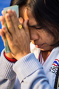 01 JANUARY 2014 - BANGKOK, THAILAND: An anti-government protestor prays during a special merit making ceremony in the protest camp. Thousands of anti-government protestors are camped out at Democracy Monument in central Bangkok protesting against the government of Yingluck Shinawatra. The protest leader, Suthep Thaugsuban, has called for residents of the Thai capital to rise up against Yingluck. He has promised to shut the city of 12 million down in his final push to overthrow the government. About 100 members of the Thailand's Buddhist clergy visited the protest site Wednesday morning for a New Year's day special merit making ceremony for the protestors.     PHOTO BY JACK KURTZ