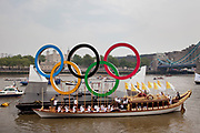 London, UK. Friday 27th July 2012. The London 2012 Olympic Games torch makes it's way up the River Thames on the final day of the torch relay. The pageant, led by the official royal barge, Gloriana arrived at it's final destination at Tower Bridge.