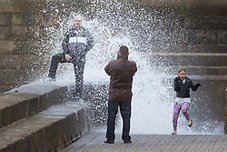 """© Licensed to London News Pictures. 09/11/2015. Bridlington, UK. FRAME 5 OF 9. A man poses for a photograph on the sea defences at the sea side town of Bridlington & gets caught out by a huge wave. The Yorkshire region was hit by severe gales this afternoon with winds up to 60mph. The Met Office warned West Yorkshire to expect gales and locally severe gales over high ground, with some """"very gusty"""" winds to the east of high ground as well.<br /> Photo credit: Andrew McCaren/LNP"""