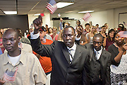 "June 21, 2010 - PHOENIX, AZ: WOL MUK, (CENTER) from Sudan, and other new citizens sing the ""God Bless the USA"" during a naturalization ceremony for former refugees at the International Rescue Committee offices in Phoenix, AZ, Monday, June 21. World Refugee Day was Sunday, June 20; the IRC and US Citizenship and Immigration Services offices  marked the day by holding a naturalization ceremony for 10 people who came to the US as refugees.  Photo by Jack Kurtz"