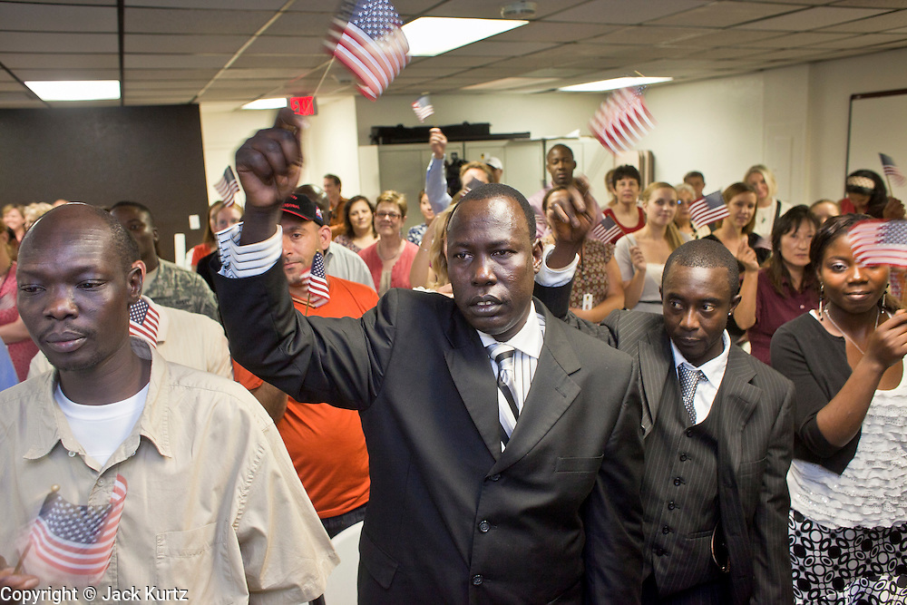 """June 21, 2010 - PHOENIX, AZ: WOL MUK, (CENTER) from Sudan, and other new citizens sing the """"God Bless the USA"""" during a naturalization ceremony for former refugees at the International Rescue Committee offices in Phoenix, AZ, Monday, June 21. World Refugee Day was Sunday, June 20; the IRC and US Citizenship and Immigration Services offices  marked the day by holding a naturalization ceremony for 10 people who came to the US as refugees.  Photo by Jack Kurtz"""