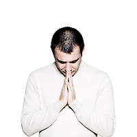 Portrait of a handsome expressive religious man praying in studio on white isolated background