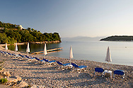 Beach chairs at sunrise on Avlaki beach in northeast Corfu, The Ionian Islands, The Greek Islands, Greece, Europe