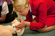 CRAWLEY, WEST SUSSEX, UK, OCTOBER 27TH 2011. Journalist / writer Andrea Sachs gives the kiss of life to a dummy in a medical training session during research on a story about Virgin Atlantic air stewardess and steward training at The Base training facility. (Photo by Mike Kemp for The Washington Post)