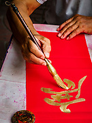 11 JANUARY 2019 - BANGKOK, THAILAND: A calligrapher writes Chinese New Year greetings on a table he set up in Bangkok's Chinatown. Calligraphers set up tables throughout Chinatown in the weeks leading up to Chinese New Year. About 14% of Thais are of Chinese ancestory and Lunar New Year is widely celebrated in Thailand. Chinese New Year celebrations in Bangkok start on February 4, 2019. The coming year will be the Year of the Pig in the Chinese zodiac.        PHOTO BY JACK KURTZ