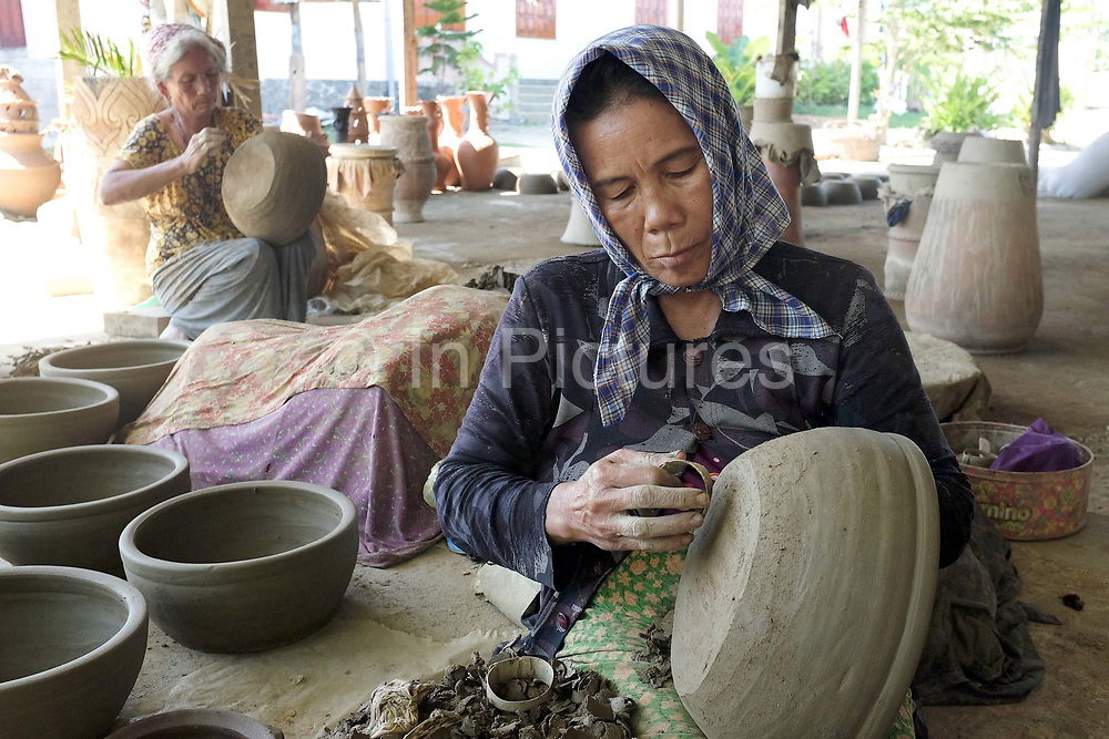 Hindu Cham women making a ceramic pot using a traditional method in the famous pottery village of Bau Truc in Central Vietnam. Cham potters do not use a wheel to make pots, instead clay is pressed into shape using the hands. Layers of clay are added to the original piece and the potter moves around the object, pressing the clay into the desired shape. They are then put directly in the sun and completely bone dried, making them ready to be fired. Firing is done in an open pit with temperatures going up to 800 degree Celcius. The pots are arranged together and covered with layers of rice straw, which is set on fire.