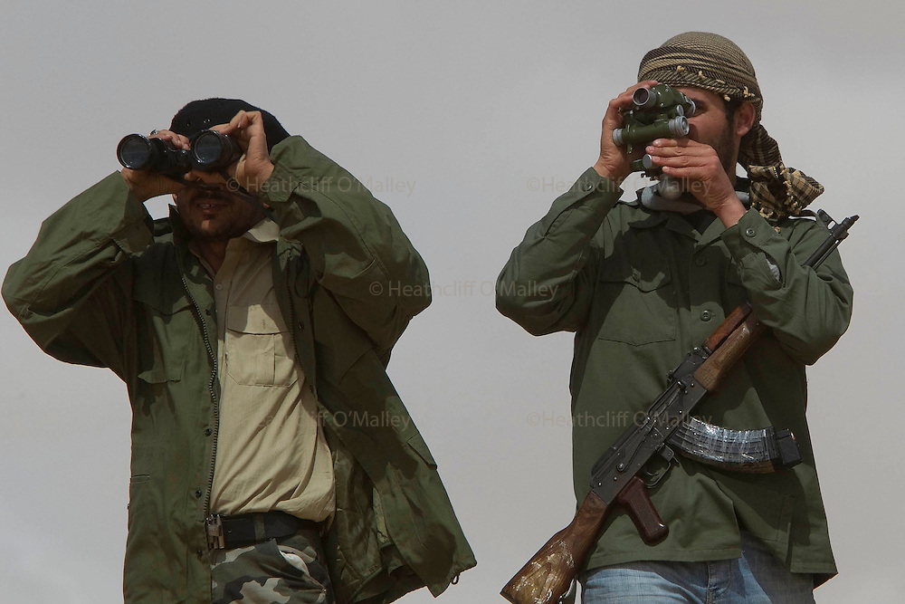 Mcc0030300 . Daily Telegraph..Rebel fighters scan the horizon on the road to Brega about 50kms from Ajdabiyah. Brega is still in the control of Gaddafi's army but the rebels appear to be better organised today and gaining ground with reports of fighting around the University...Brega 1 April 2011