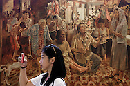 A woman takes a picture with her smart phone in Antipolo Museum, Rizal Province, Luzon Island, Phillipines, Southeast Asia