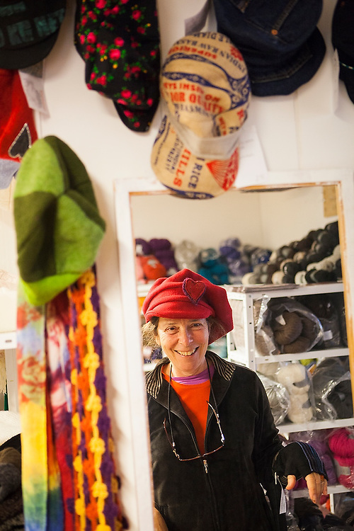 Liana Welty tries on handmade hats at Aina Johansen's boutique Kaosheimen in Sorland, Vaeroy Island, Norway.