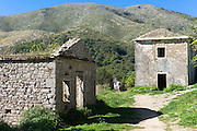 Tourists view derelict old stone houses ruins in ancient mountain village of Old Perithia - Palea Peritheia - Northern Corfu, Greece